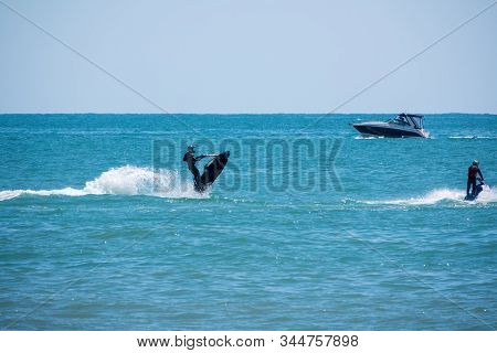 A Man Quickly Rides A Jet Ski In The Blue Sea. Young Man On Jet Ski. Professional Jet Ski Rider. Jet