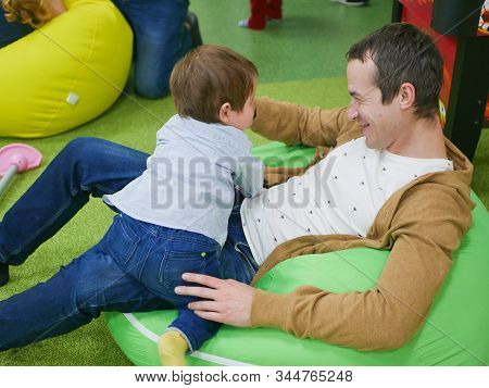 Young Father With His Son In The Playroom. Happy Young Father Plays With His Cute Little Smiling Son