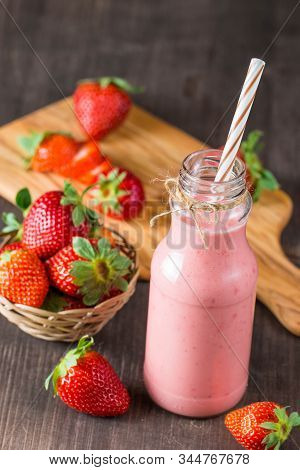Glass Of Fresh Strawberry Milkshake, Smoothie And Fresh Strawberries On Pink, White And Wooden Backg