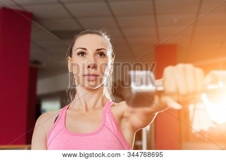 Strong Beauty Fitness Coach Wearing Pink And Black Professional Sportswear Holding A Dumbbell In A G
