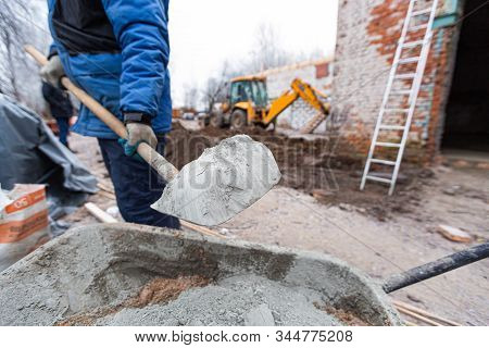 Worker In Protect Gloves Is Loading The Cement By Shovel To Building Trolley With Sand To Making The