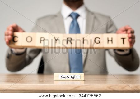 Selective Focus Of Wooden Block With Word Copyright Near Businessman Holding Wooden Cubes With Copyr