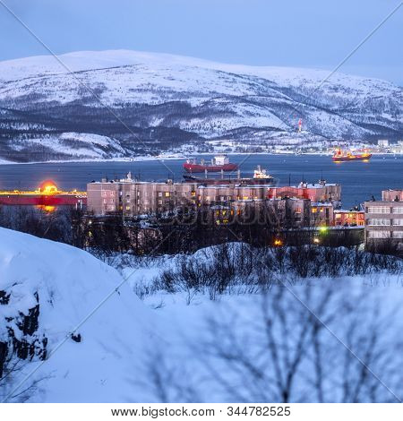 Murmansk, Russia - January, 5, 2020: Non-freezing seaport in the city of Murmansk in winter. The picture was taken at 2 p.m. in natural light at the height of a polar night