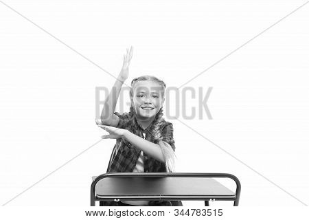 Smart Pupil. Primary School Pupil. Small Pupil Raising Hand At Desk Isolated On White. Little Pupil