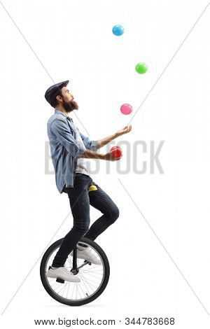 Full length profile shot of a man riding a unicycle and juggling with balls isolated on white background