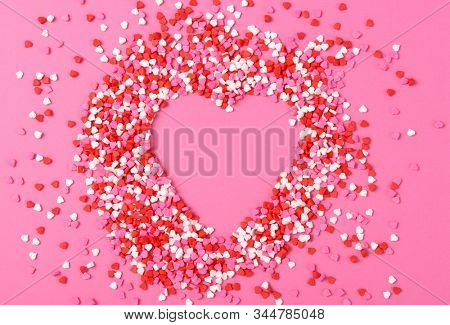 Valentined Day Concept: Heart Shaped candy sprinkles on a pink surface forming a larger heart shape.