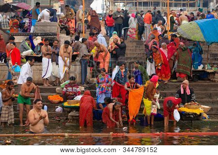 VARANASI, INDIA, JANUARY 18, 2019 : Traditional Ganges river bathing and Hindu ritual at sunrise along the Varanasi Ghats