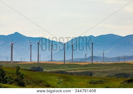 A Large Wind Turbine Farm Is Seen By The Rocky Mountains In Alberta, Canada. Clean Renewable And Gre