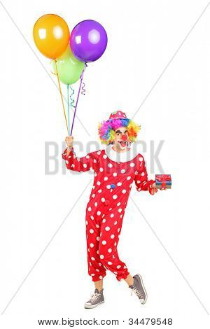 Full length portrait of a male clown, happy joyful expression on face, with a bunch of balloons and a gift isolated on white background
