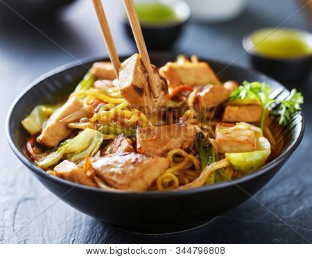 eating chicken yakisoba with chopsticks