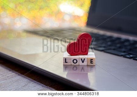 Online Dating Concept With Laptop Red Heart Shape And Wooden Word Love