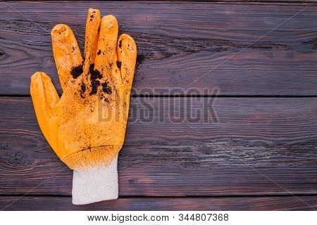 Dorty Gardening Glove With Soil. Freespace On Wooden Background.
