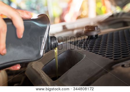 Pouring Oil To Car Engine. Fresh Oil Poured During An Oil Change To A Car. Hand Mechanic In Repairin