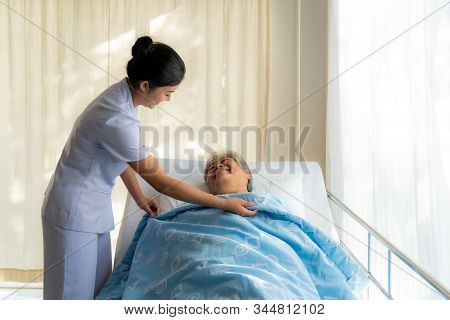 Elderly Woman In Bed And Nurse Cover Blanket To Her. Old Asian Woman And Beautiful Asian Nurse Woman