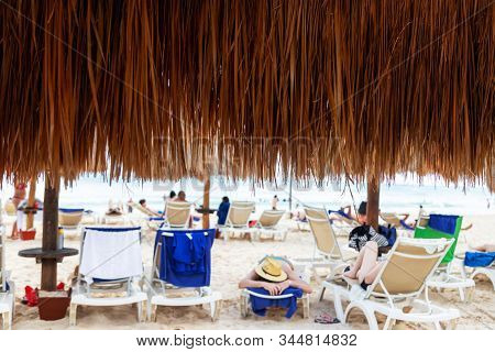 Close Up Of Coconut Palm Leaf Beach Umbrella With Beachgoers Relaxing At A Distance In A Cancun Beac