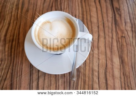 White Cup Of Cappuccino With Latte Art On Wooden Background. Beautiful Foam, Ceramic Cup, Copy Space