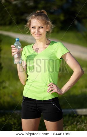 Attractive female during her workout in the park, holds blue bottle of water