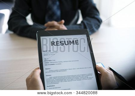 Executives Are Interviewing And Watching The Resume Via Tablet. Focus On Resume Writing Tips, Applic