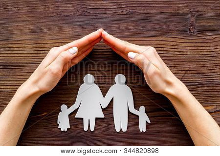 Live Insurance Concept. Family Silhouette Under Palm On Dark Wooden Background Top-down