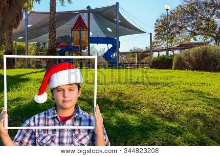 Handsome boy in Santa Claus hat smiling holding a frame in his hands. Children 's playground with a multicolored attractions. The concept of physical and mental development of children