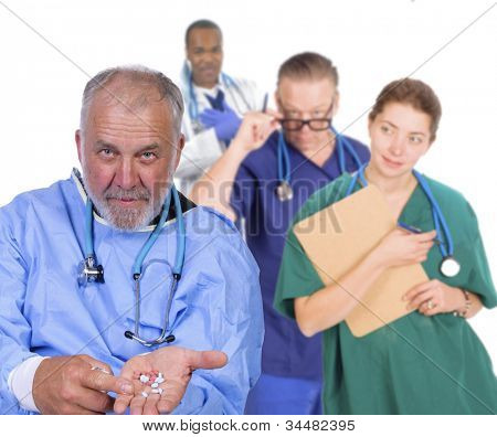 Portrait of an older doctor holding his hand out with pills, standing in front of his team smiling