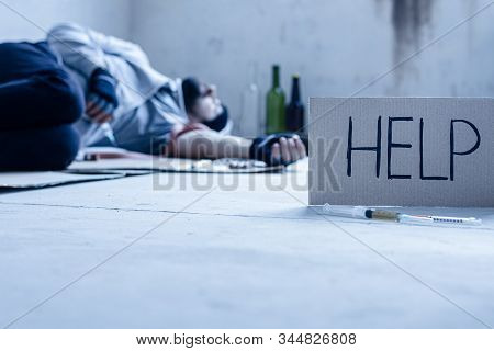 Closeup Inscription Help, Syringes. On Background Young Junkie Homeless Addict Man Is Sleeping After