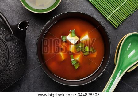 Miso traditional japanese soup with tofu and spring onion. With green tea in pot and bowls. Top view