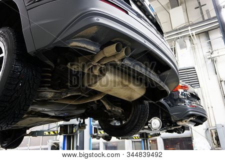 A Modern Car Suv In A Service Center Is Lifted On A Lift For Diagnosics, Maintenance Or Repair. Clos