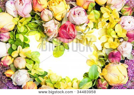 Beautiful ornamental wreath in the shape of heart of made multicolored roses isolated on white