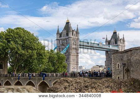 London, UK - 7th June 2017: Tourists walk along the rampart walls of the Tower of London, and enjoy the views to the famous Tower Bridge. In the City of London, England.