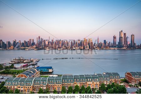 New York, New York, USA downtown city skyline on the Hudson River at dusk.