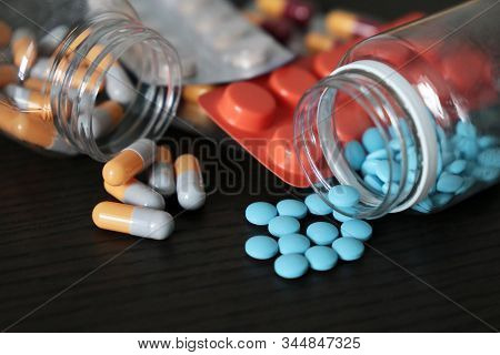 Pills And Capsules On Dark Wooden Table, A Lot Of Multicolored Medication Close-up. Concept Of Pharm