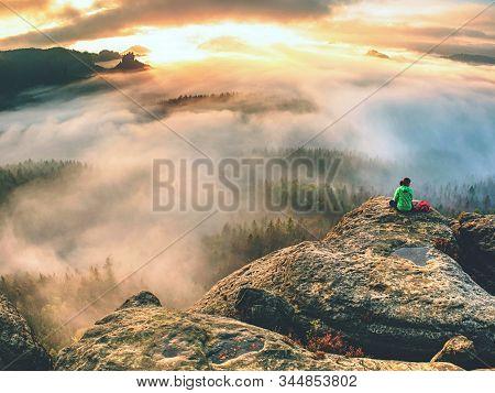 Female Hiker Takes A Break And Enjoys Mountain Views.  Female Hiker Backpacker Sitting On The Peak E