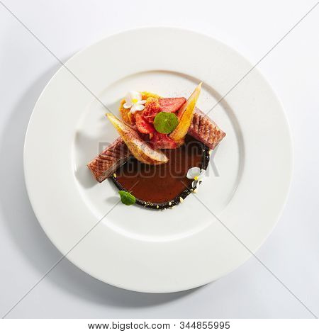 Duck breast with stewed pear, flowers and strawberries on restaurant plate isolated.Cooked poultry fillet in brown sauce, delicious dinner dish topview