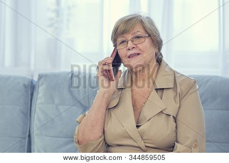 Old Lady Talking On Mobile Phone, Smiling, Looking Away.