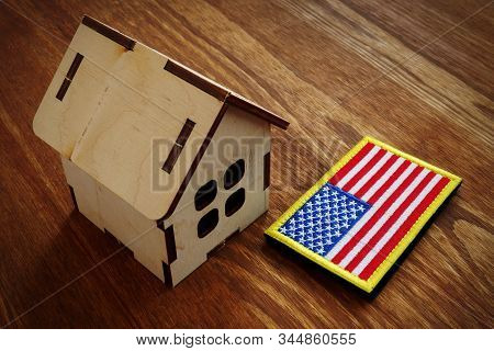 American Flag And Small House. Va Mortgage Loan Concept.
