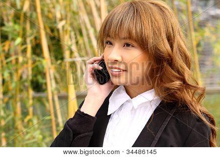 beautiful asian woman using smart phone in the park