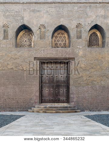 Aged Wooden Weathered Door, Perforated Arched Stucco Window Decorated With Floral Patterns, And Thre