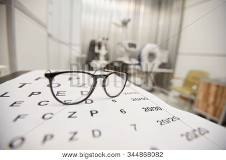 Background Image Of Glasses Lying On Eye Chart In Ophthalmology Office, Vision And Eye Test Concept,