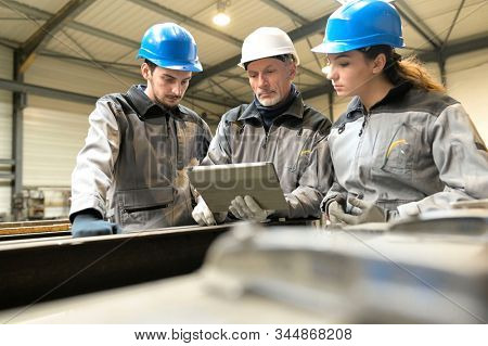 Steelwork instructor with young apprentice in workshop