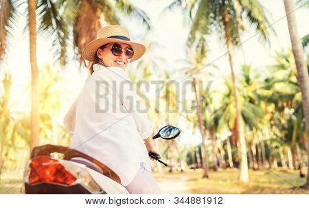 Happy Smiling Woman In Straw Hat And Sunglasses Riding Motorbike Under Palm The Trees. Careless War