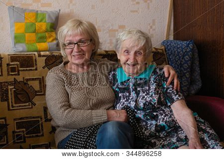 An elderly woman with her adult daughter cuddling on couch.