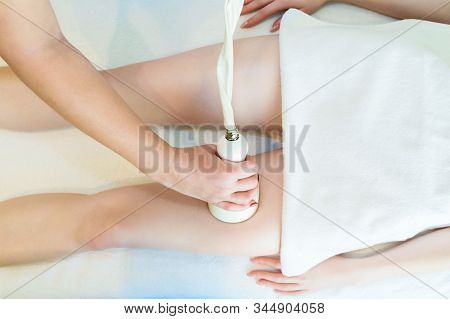 Body Massage By Cavitation. A Young Girl On A Massage Table Anti-cellulite Massage Of Thighs.