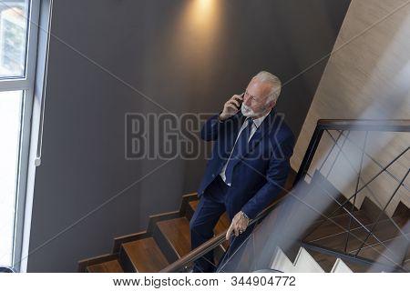 Senior Businessman Walking Down The Modern Office Building Stairway, Having A Phone Conversation Whi