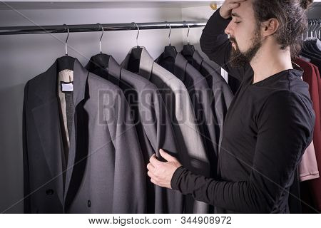 Closeup Portrait Of A Thousand-year-old Young Bearded Guy In A Mens Clothing Store, Chooses A Busine