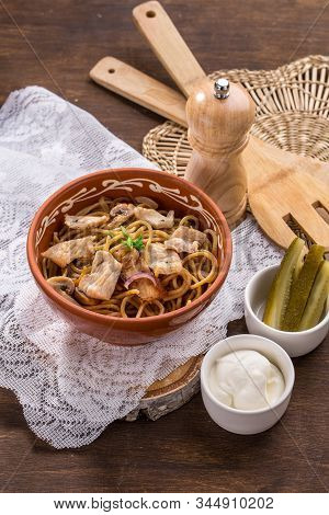 Spaghetti With Mushroom And Meat In Clay Pot On Wooden Table