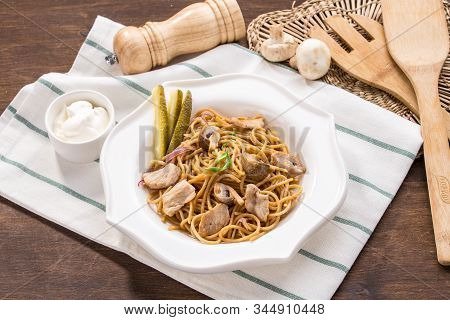 Spaghetti With Mushroom And Meat On White Plate On Wooden Table