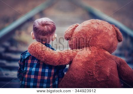 A Little Boy With A Big Teddy Bear Is Sitting On The Railway Tracks. Loneliness And Sadness Of A Chi