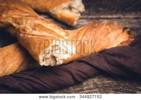 French Baguette On Rustic Wooden Background. Broken Baguette, Close Up. Healthy Organic Baguette Sli