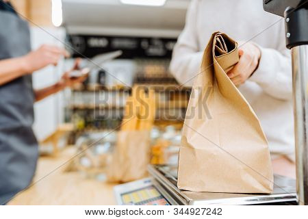 Woman Chooses And Buys Products In Zero Waste Shop. Weighing Dry Goods In Plastic Free Grocery Store